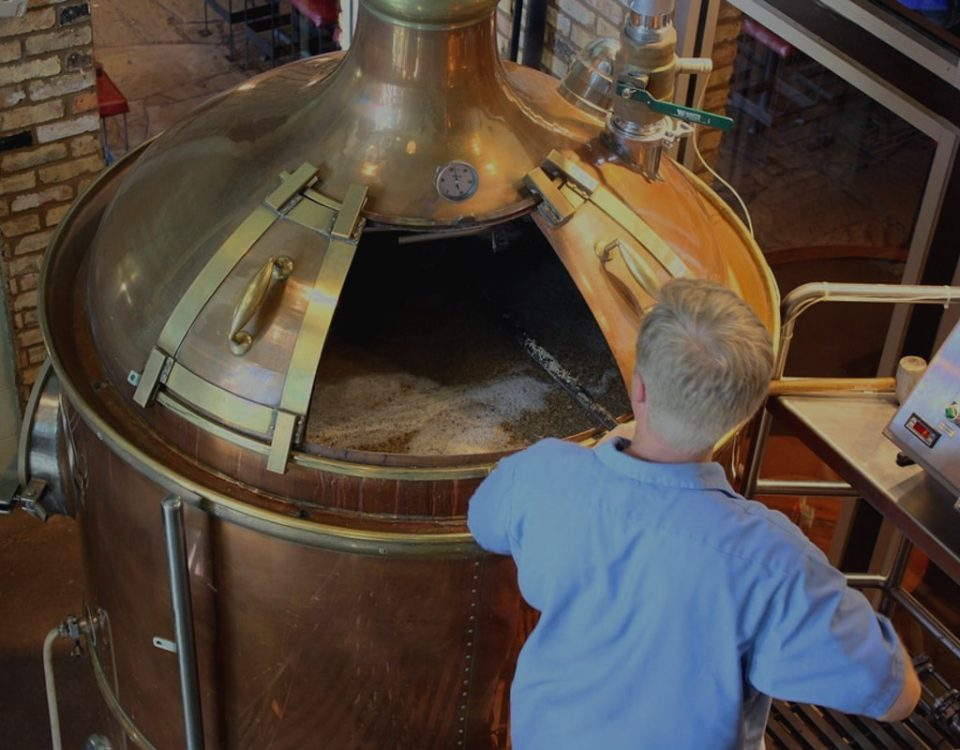 Hombre fabricando cerveza artesanal en alambique de cobre