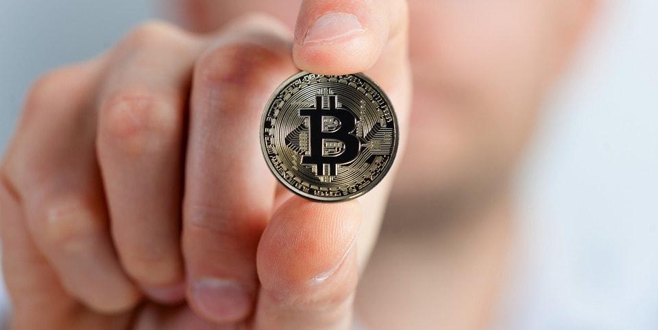 mano que sostiene un bitcoin