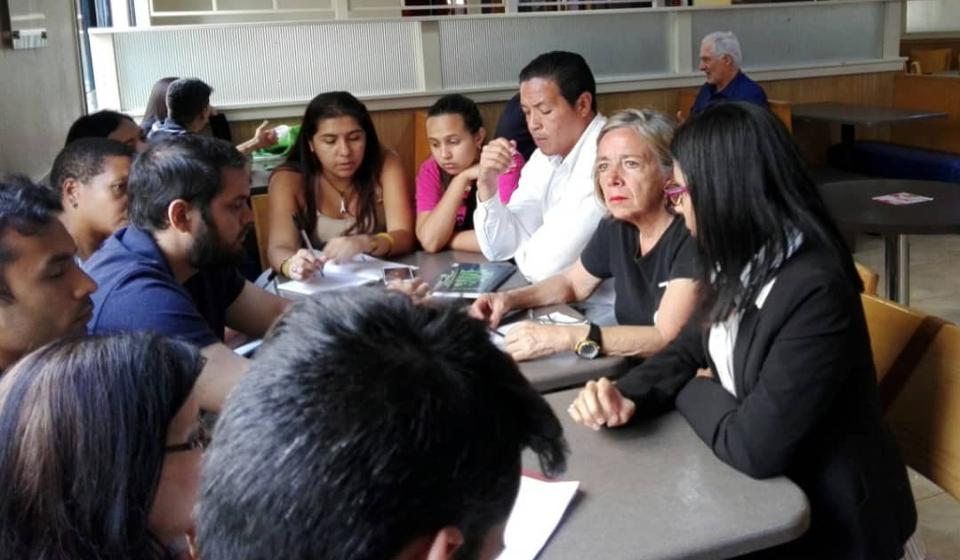 Legal media dirigiendo conversatorio presencial a un grupo de emprendedores