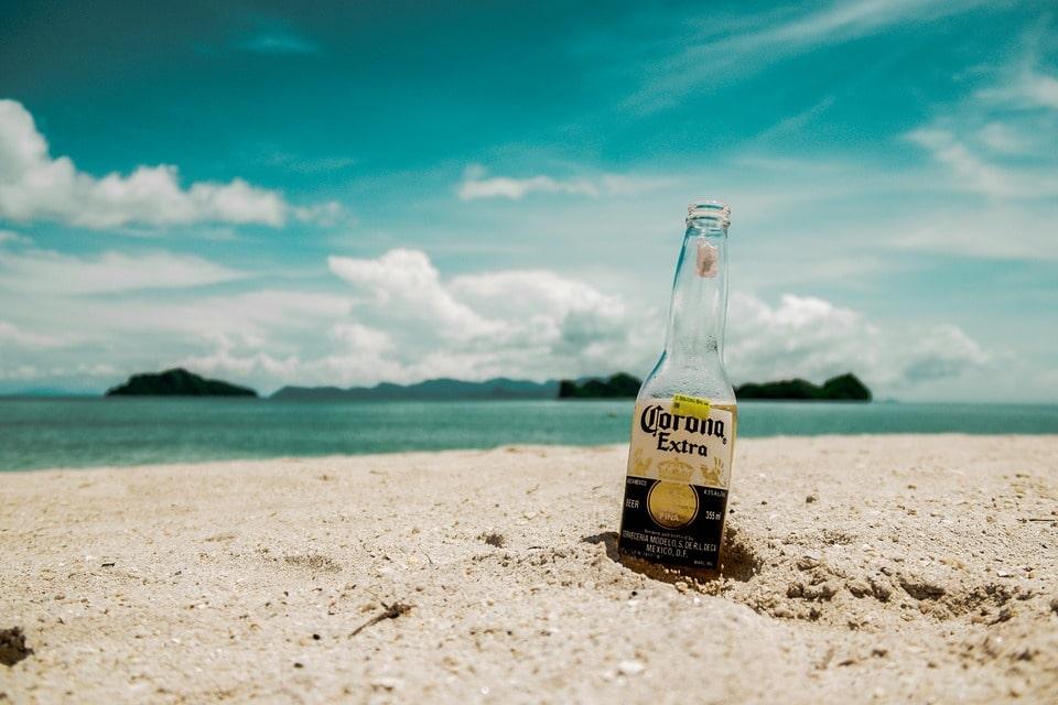 Botella de cerveza marca Corona, enterrada en arena